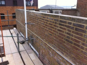Re building a damaged parapet wall and repointing.